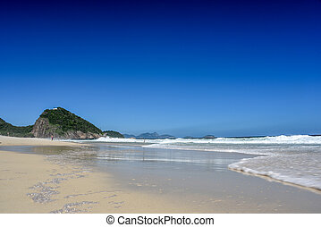 The coast of Atlantic Ocean at Leme beach with Forte Duque de Caxias, mountains and bright blue sky on the background