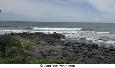 The coast of the tropical sea in sunny day, Waves run on the coast with black stones