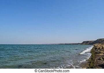 The coastline of Azov sea. Sea waves from a rocky shore.