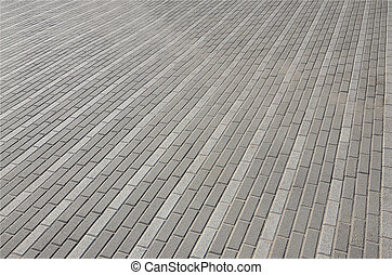 The cobblestones road in town square. Background texture in perspective