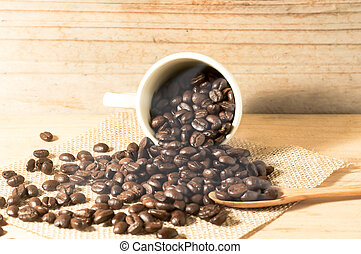 the coffee bean and cup of coffee on sack with spoon on wooden table background. still life process