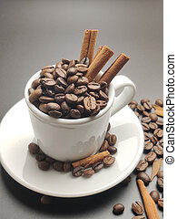 the coffee beans in a Cup with cinnamon sticks on black background