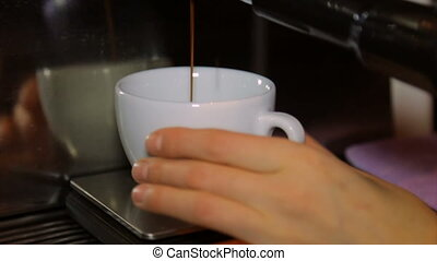 The coffee machine drains coffee into ceramic white cups -...