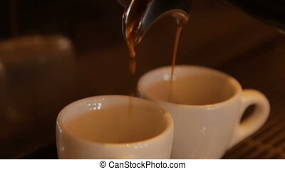 The coffee machine drains coffee into ceramic white cups -...