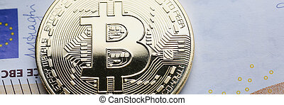 The coin of crypto currency bitcoin against background euro ...