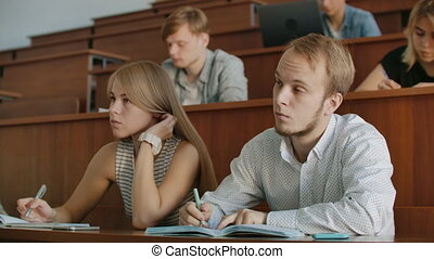 The college current audience in which students listen to the teacher and write a short film report in the notebook. Transfer knowledge and educate students.