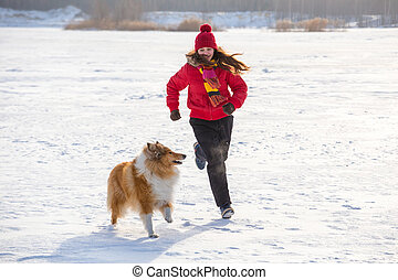 The Collie dog running with girl at winter landscape