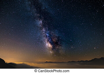 The colorful glowing core of the Milky Way and the starry sky captured at high altitude in summertime on the Italian Alps, Torino Province. Mars and Saturn on the right.