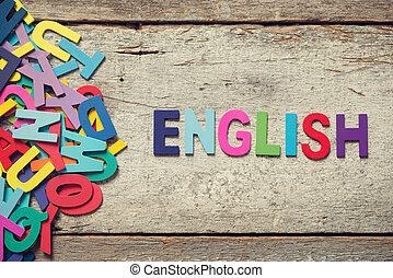 "The colorful words ""ENGLISH"" made with wooden letters next to a pile of other letters over old wooden board."