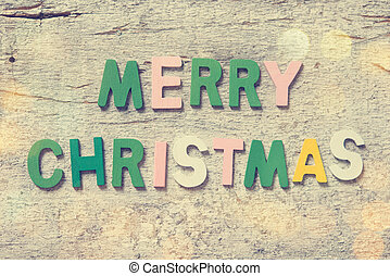 the colorful words merry christmas made with wooden letters on old wooden board