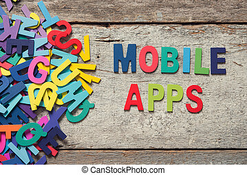 """The colorful words """"MOBILE APPS"""" made with wooden letters next to a pile of other letters over old wooden board."""