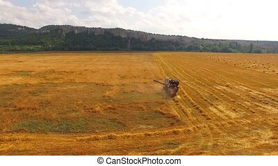 The combine harvests wheat, in the distance mountains and...