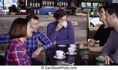 The company of middle-aged friends communicate in a small restaurant, where they ordered dinner on the menu. Drug-chatting and drinking American coffee from cups