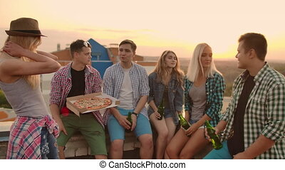 The company of six young people communicate with each other on the roof with pizza and beer. Girls look around at summer sunset.