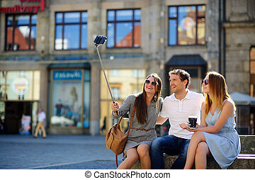 The company of young friends is photographed on the city square.