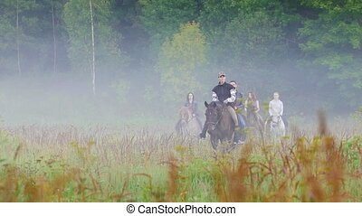 The company of young people walking on horseback in nature,...
