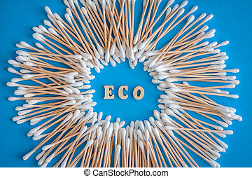 The composition is a round frame of wooden cotton swabs on a blue background and the words natural, eco-friendly. Flat lay. Copy space. Trend The concept is natural, eco-friendly, modern hygiene.