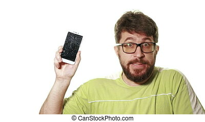 The concept of a broken gadget. Bearded angry man showing broken smartphone screen.
