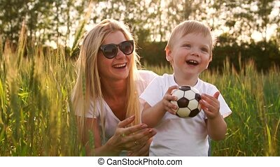The concept of a happy family. Close-up of a boy and his mother in a field with wheat spikes smiling and playing with a soccer ball
