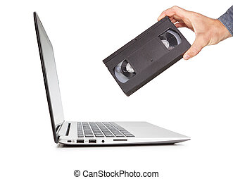 The concept of a video cassette technology in the hand compared to the laptop. Progress on multimedia and information.