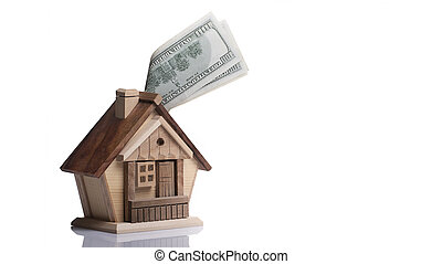The concept of accumulating savings for the purchase of real estate. Small wooden lodge piggy bank, and 100 banknotes.