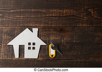 The concept of buying a home. Decorative hut and house keys on a brown wooden background with a place for an inscription. top view