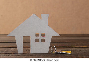The concept of buying a home. Decorative hut and house keys on a brown wooden background with a place for an inscription.