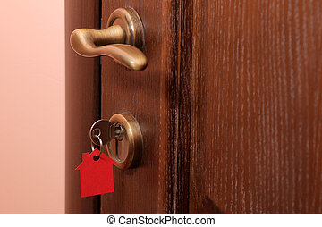 The concept of buying a home. Keys with keychain house in the door lock close-up