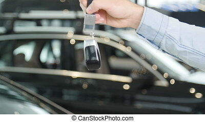 The concept of buying or renting a car. Hand with keys from the new car indoors