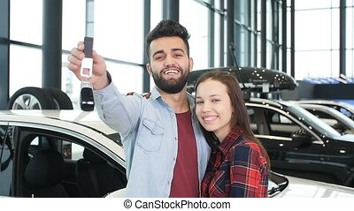The concept of buying or renting a car. Young happy interracial couple with new car keys