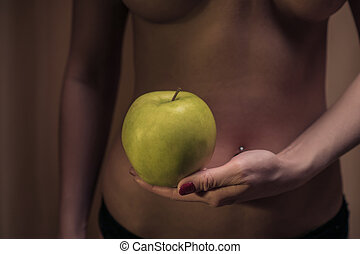 The concept of diet. Sexy female waist and an apple against the background of a woman's body. Healthy lifestyle