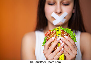 The concept of diet woman with sealed mouth keeps greasy burger