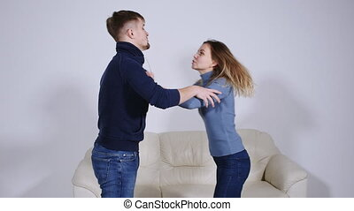 The concept of domestic violence. A man beats a young woman at home.