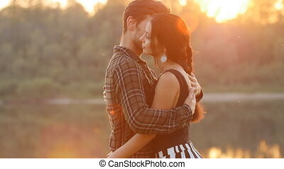 The concept of family and relationships. Young couple in love hugs at sunset