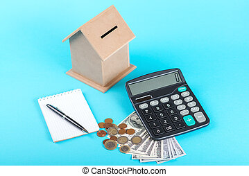 The concept of financial savings to buy a house. Money box, dollars, coins and calculator isolated on blue background.