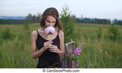 Slim girl in black dress works of flowers at sunset