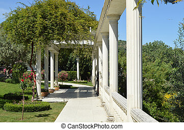 The concept of landscape design in the garden, a beautiful trellis with a column, flowers and trees