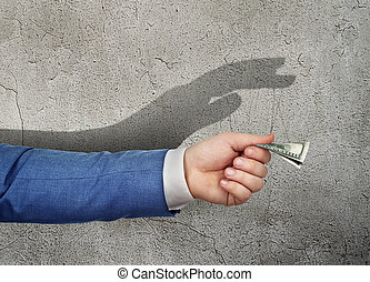 The concept of manipulation. The hand giving money casts a shadow in the form of a puppeteer's hand.