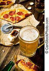 Pepperoni pizza with beer on a wooden table.