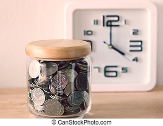 The concept of saving money , a clock is behind the scenes with filter effect retro vintage style