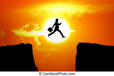 The concept of the pursuit of success. Man jump through the abyss between rocks on sunset background.