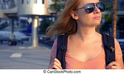 The concept of tourism. Woman tourist in sunglasses with a backpack on her back goes to the airport on the background of the plane. woman blonde smiling at the airport