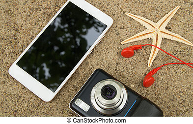 The concept of travel planning and vacation on the sea sand. Top view smartphone, camera, starfish, headphones