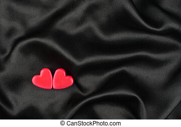 The concept of two lovers hearts lying on the black satin