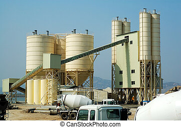 A shot of cement factory with mixer trucks