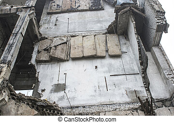 The concrete wall of the destroyed large building with hanging concrete slabs on the reinforcement. Background
