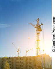 the construction crane and the building against the blue sky and sun