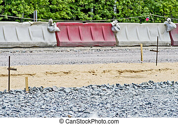 The construction of the road, fencing the roadside during the laying of the pavement. Background