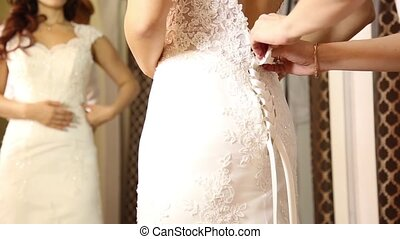 The consultant helps the young woman try a wedding dress. Girl happy to selected wedding dress. young bride makes selfie on your phone