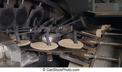 The conveyor automatic lines for the production of ice cream cones. Wafer cups and cones. Large industrial production. A major supplier of ice cream to the retail network